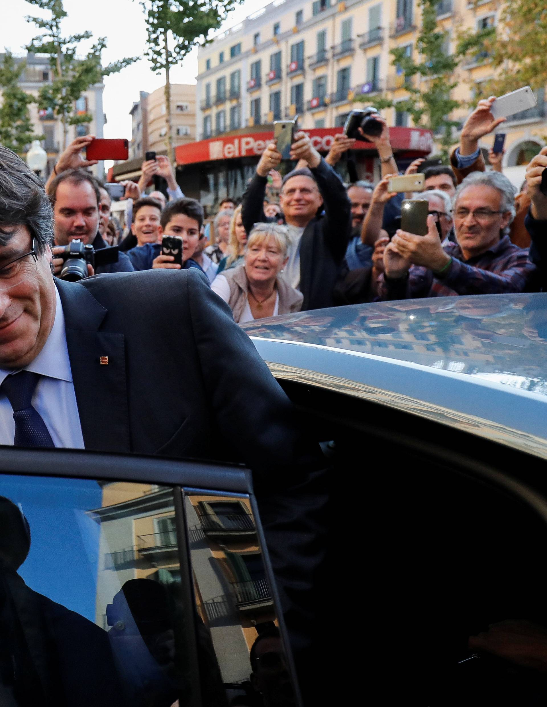 Sacked Catalan President Carles Puigdemont gets into his car after a walkabout through the center of town the day after the Catalan regional parliament declared independence from Spain in Girona