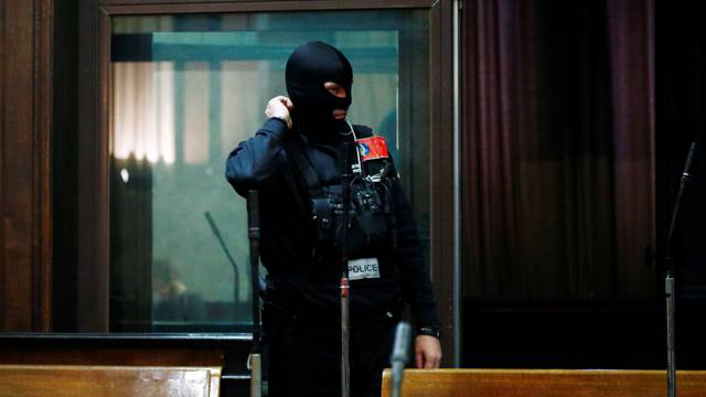 A masked police officer is pictured during the trial of Nemmouche and Bendrer at Brussels' Palace of Justice