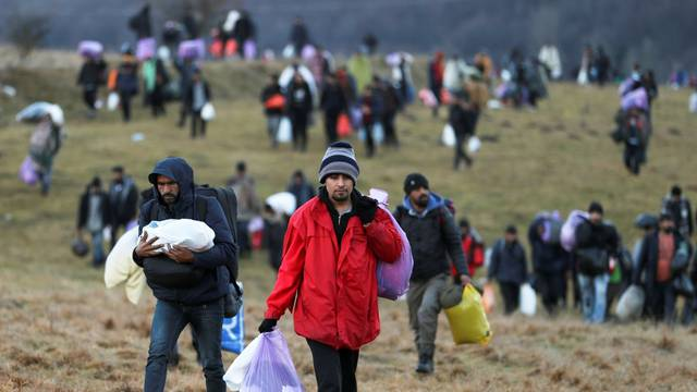 """Migrants walk towards the forest after camp """"Lipa"""" was closed, in Bihac"""