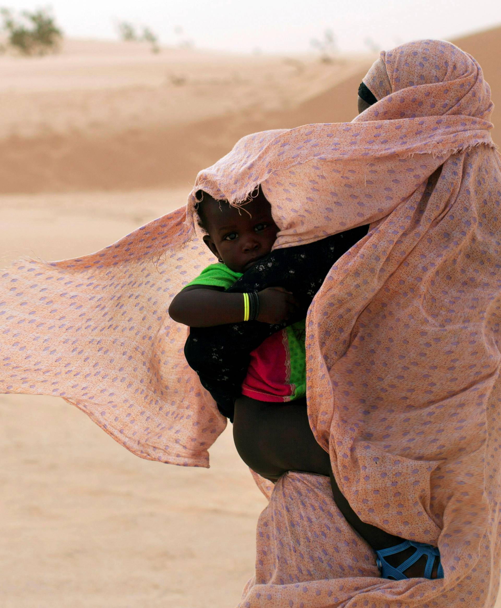 FILE PHOTO: A woman shields her child from the wind while walking on sand dunes in Nouakchott