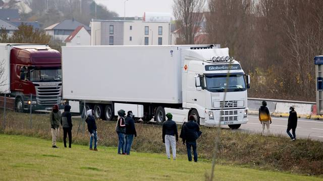 Migrants stand on roadside in hope of hiding inside trucks in Calais