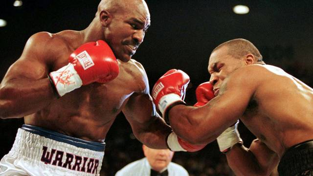 FILE PHOTO: WBA Heavyweight Champion Evander Holyfield (R) connects to the jaw of challenger Mike Tyson in the f..