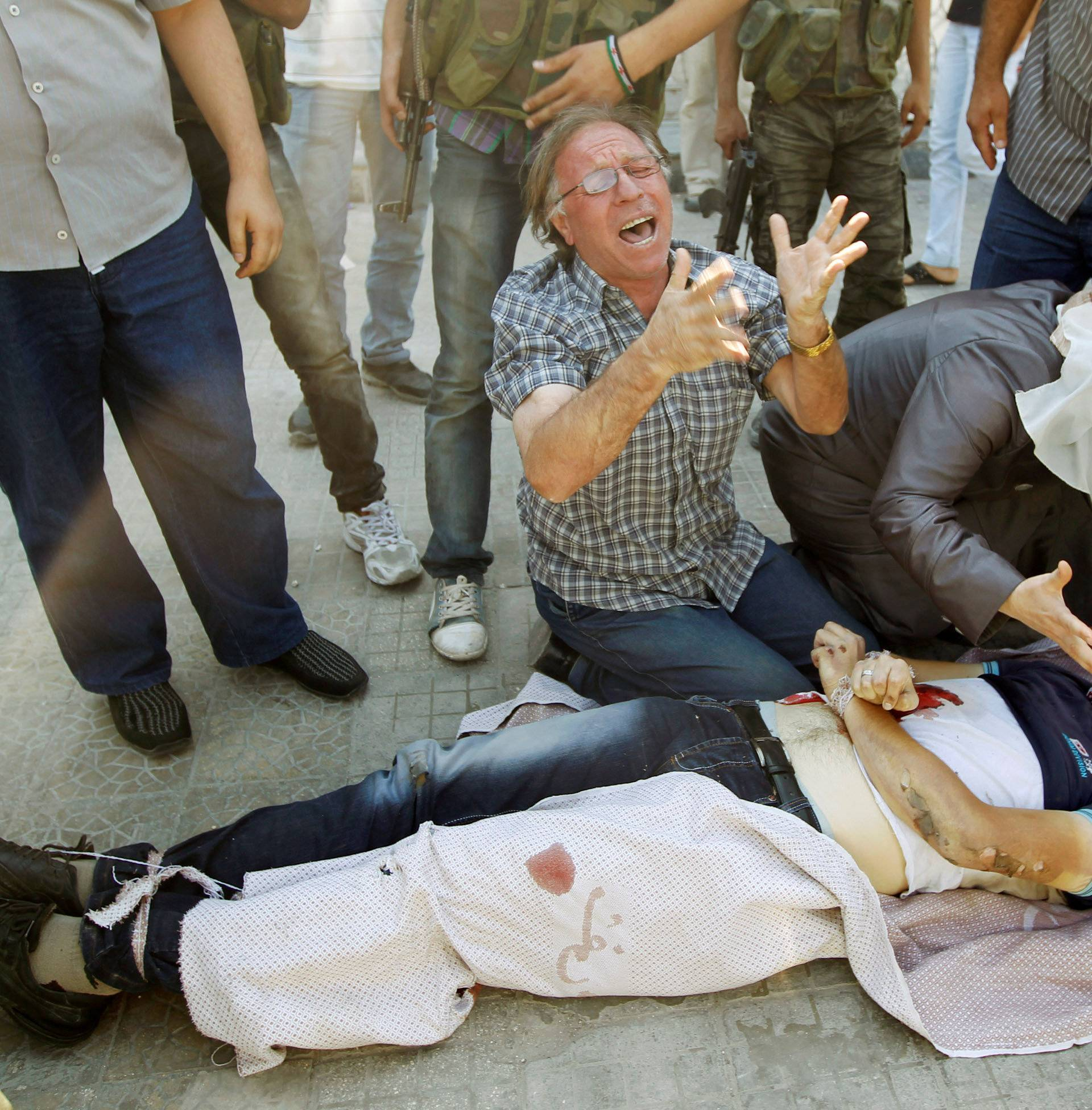 FILE PHOTO: A man and woman cry over the body of their son in Aleppo