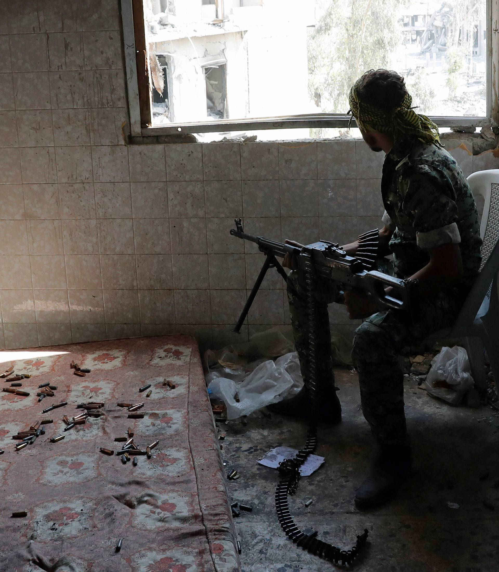 A fighter of Syrian Democratic Forces takes up a position inside a building at the frontline in Raqqa