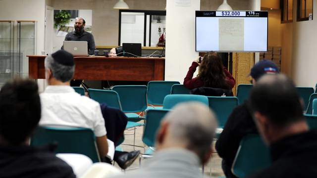 People attend a public auction where a letter written in 1922 by physicist Albert Einstein is put up for sale at Kedem Auction House in Jerusalem