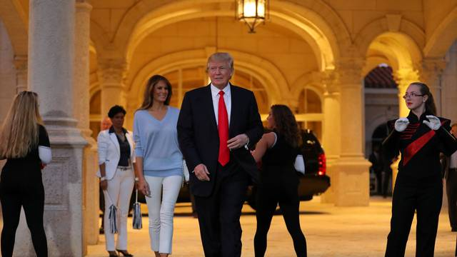 U.S. President Donald Trump and First Lady Melania Trump greet a marching band as they arrive at Trump International Golf club to watch the Super Bowl LI between New England Patriots and Atlanta Falcons in West Palm Beach, Florida, U.S.