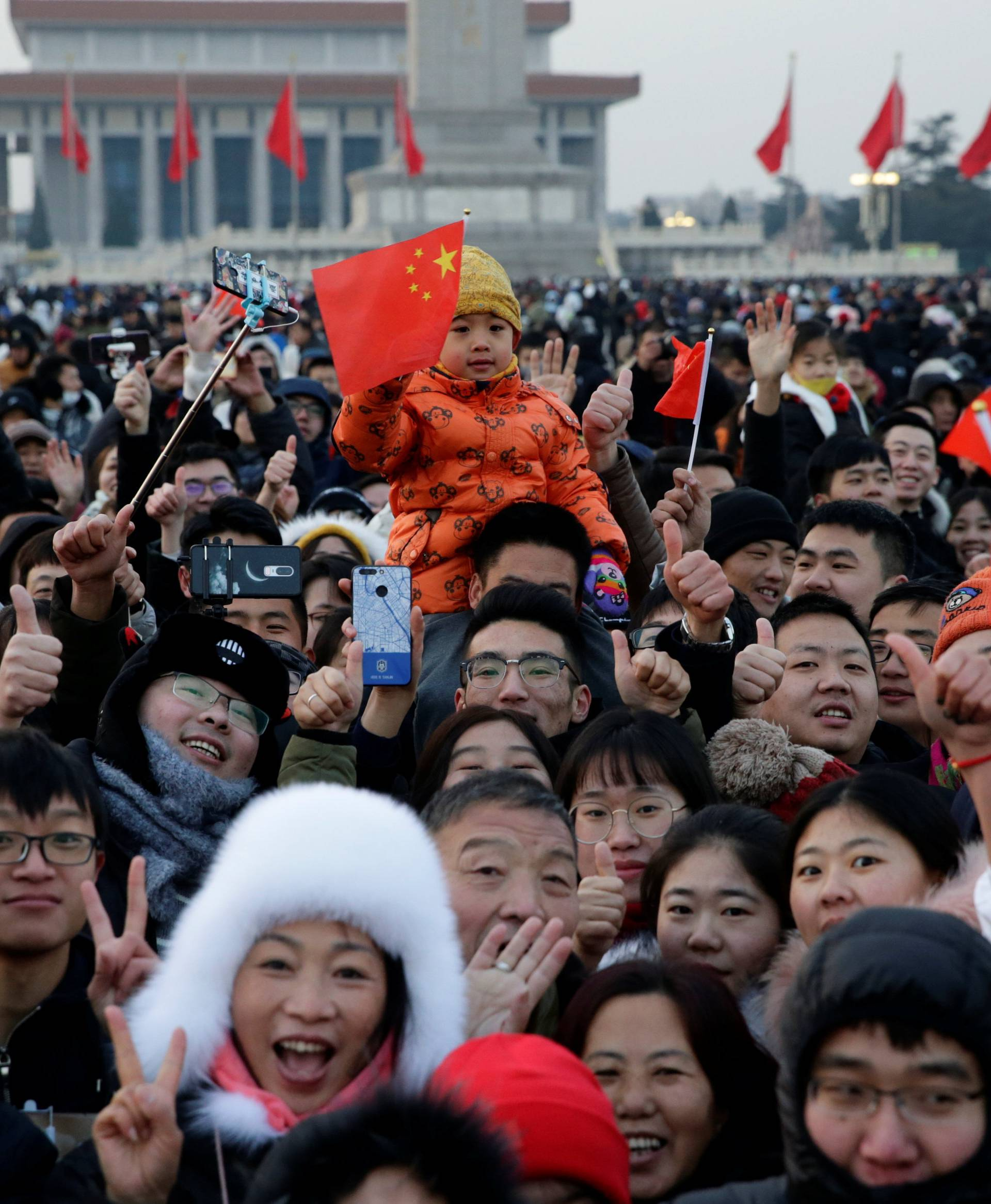 People gather on the Tiananmen Square for the flag-raising ceremony to mark the New Year in Beijing
