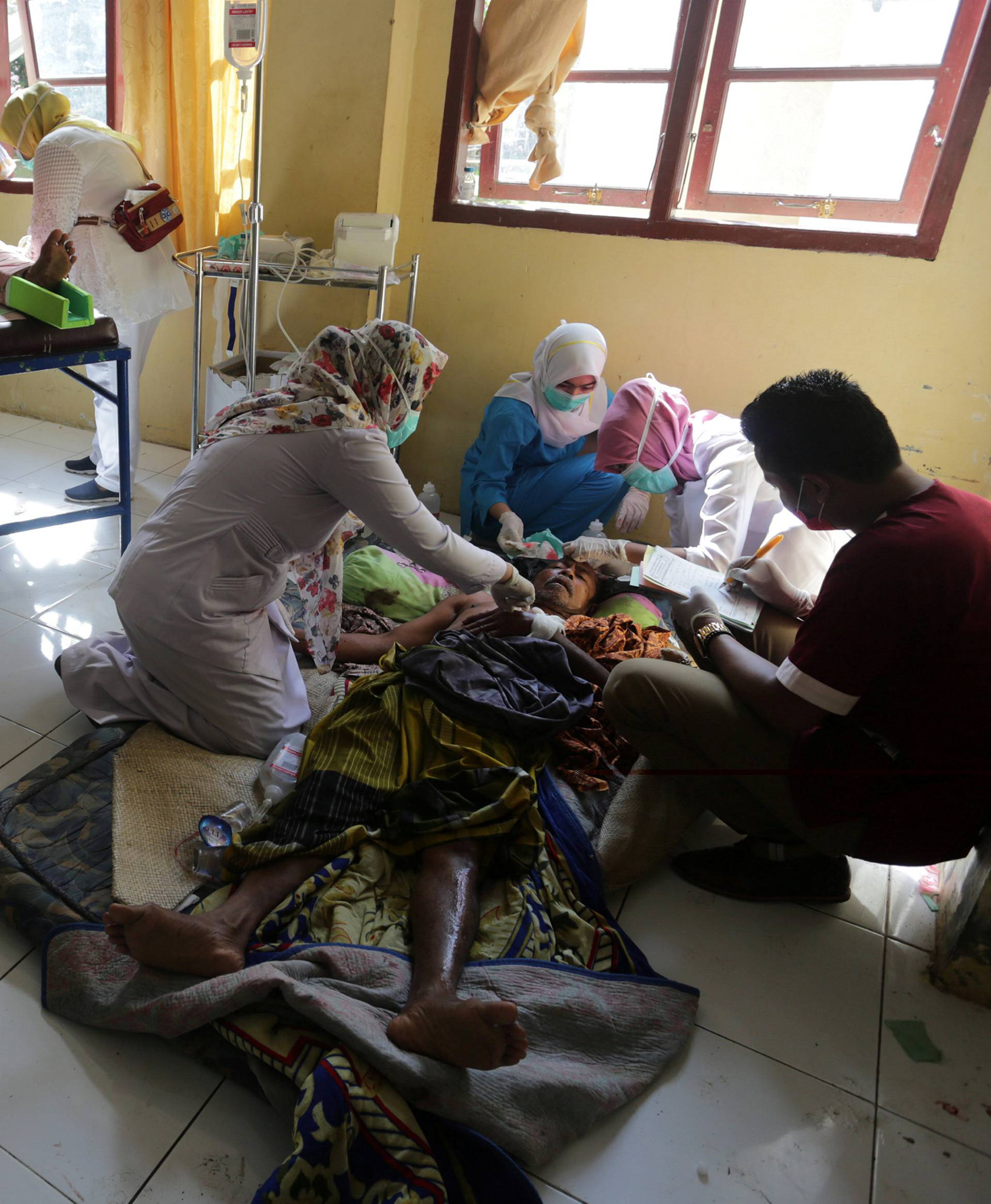 Injured people receive medical attention at a hospital following an earthquake in Sigli, Pidie regency, in the northern province of Aceh