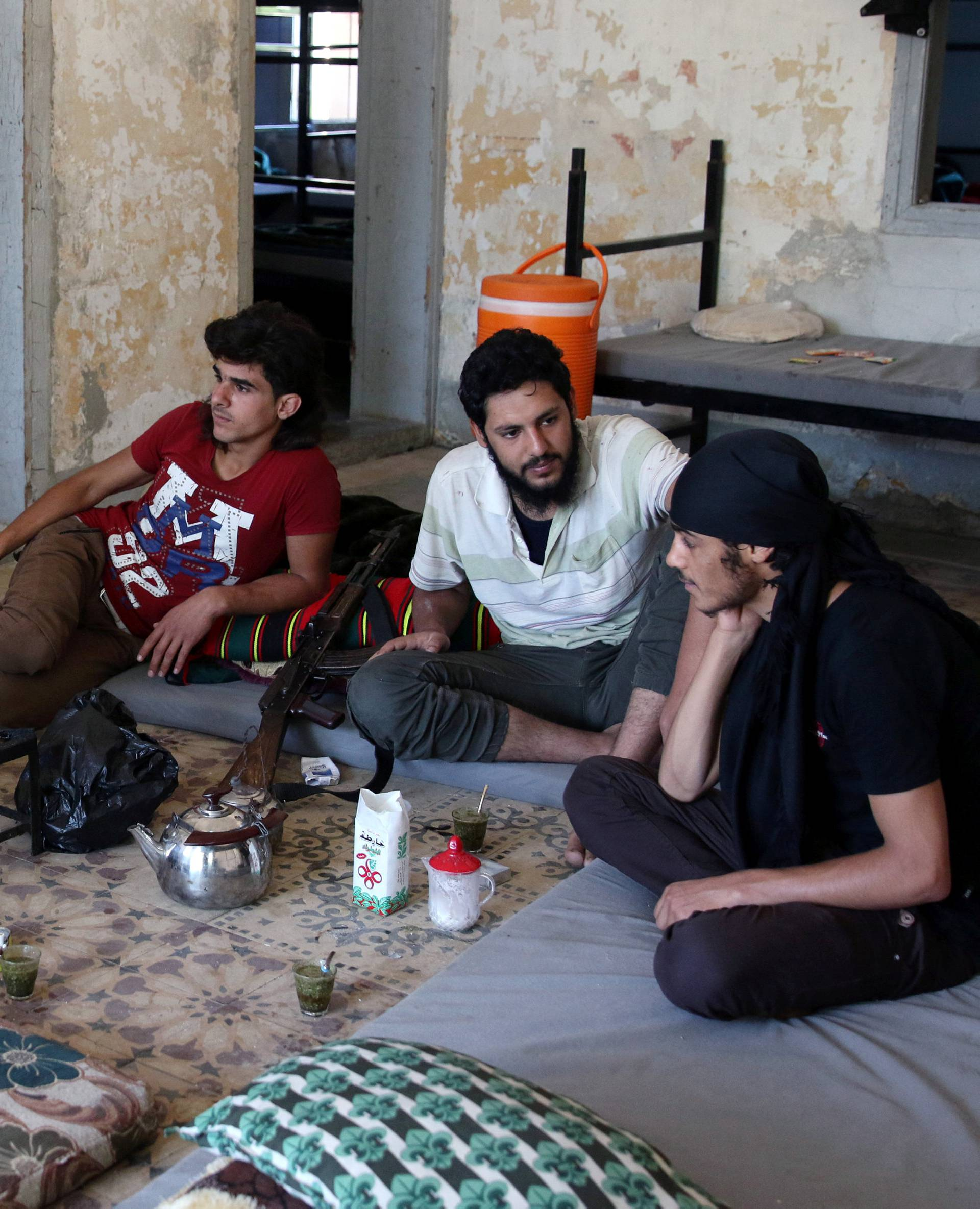 Free Syrian Army fighters rest inside a room in Quneitra