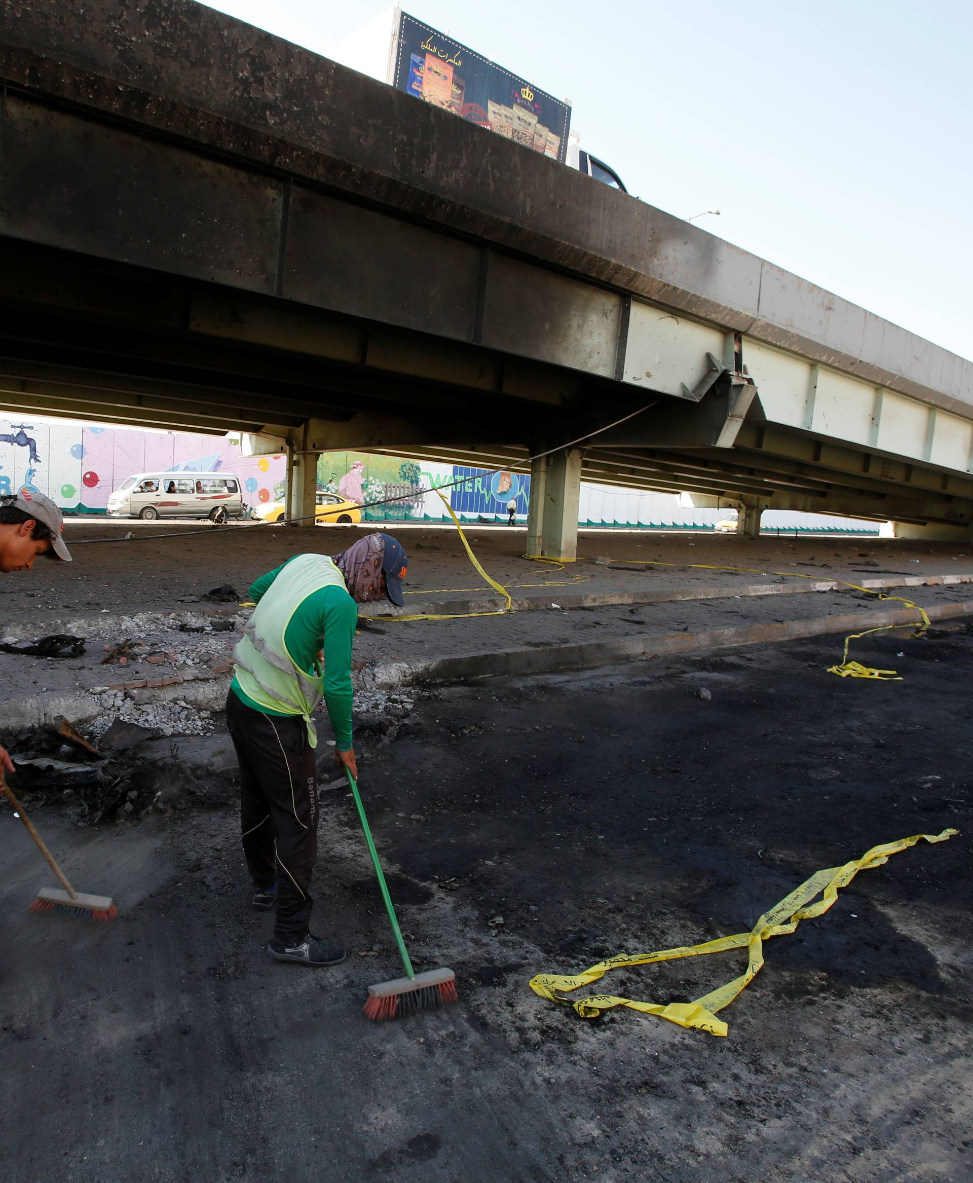 Municipal workers sweeps the ground at the site of a suicide bomb attack at Nakheel Mall across from the oil ministry, in Baghdad