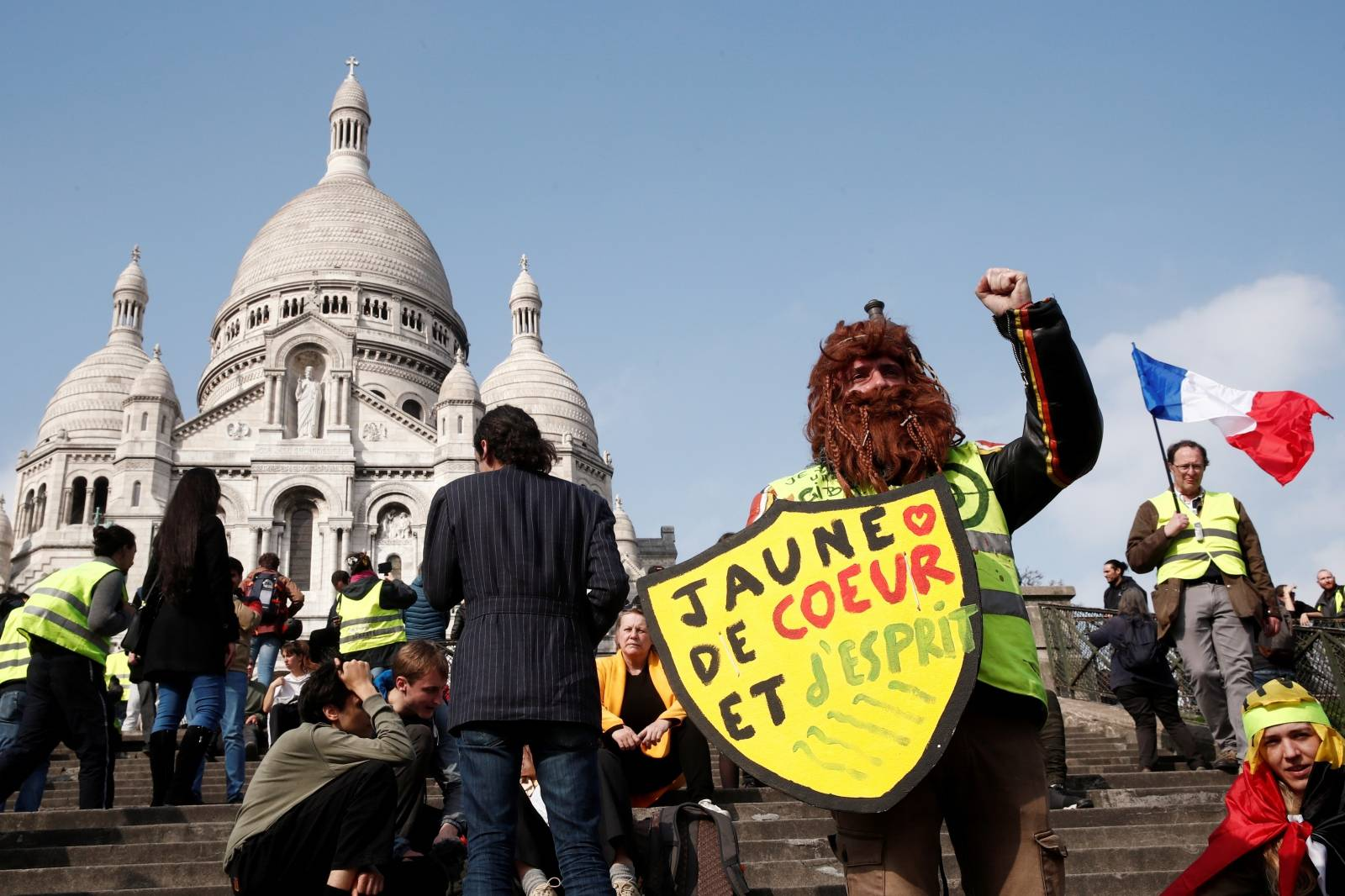 "Protesters wearing yellow vests attend a demonstration in front of the Sacre-Coeur Basilica of Montmartre during the Act XIX (the 19th consecutive national protest on Saturday) of the ""yellow vests"" movement in Paris"