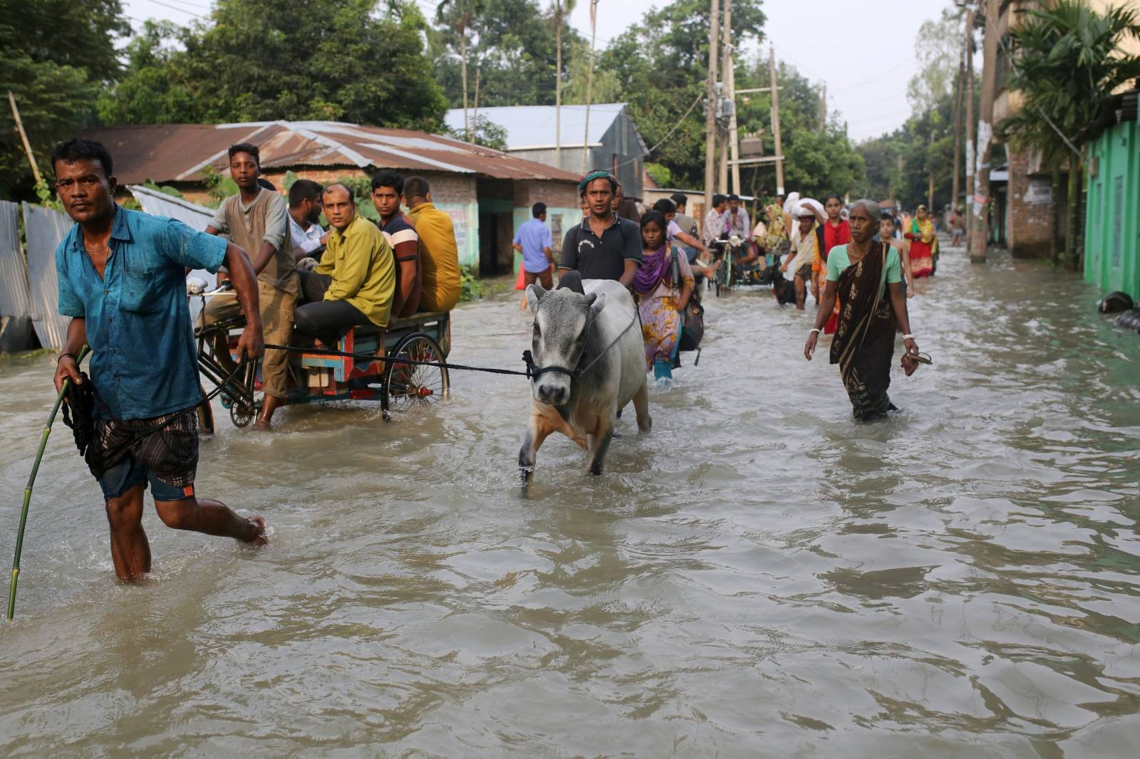 People move along a flooded road in Gaibandha