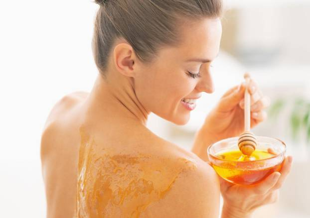 Happy young woman enjoying honey spa therapy