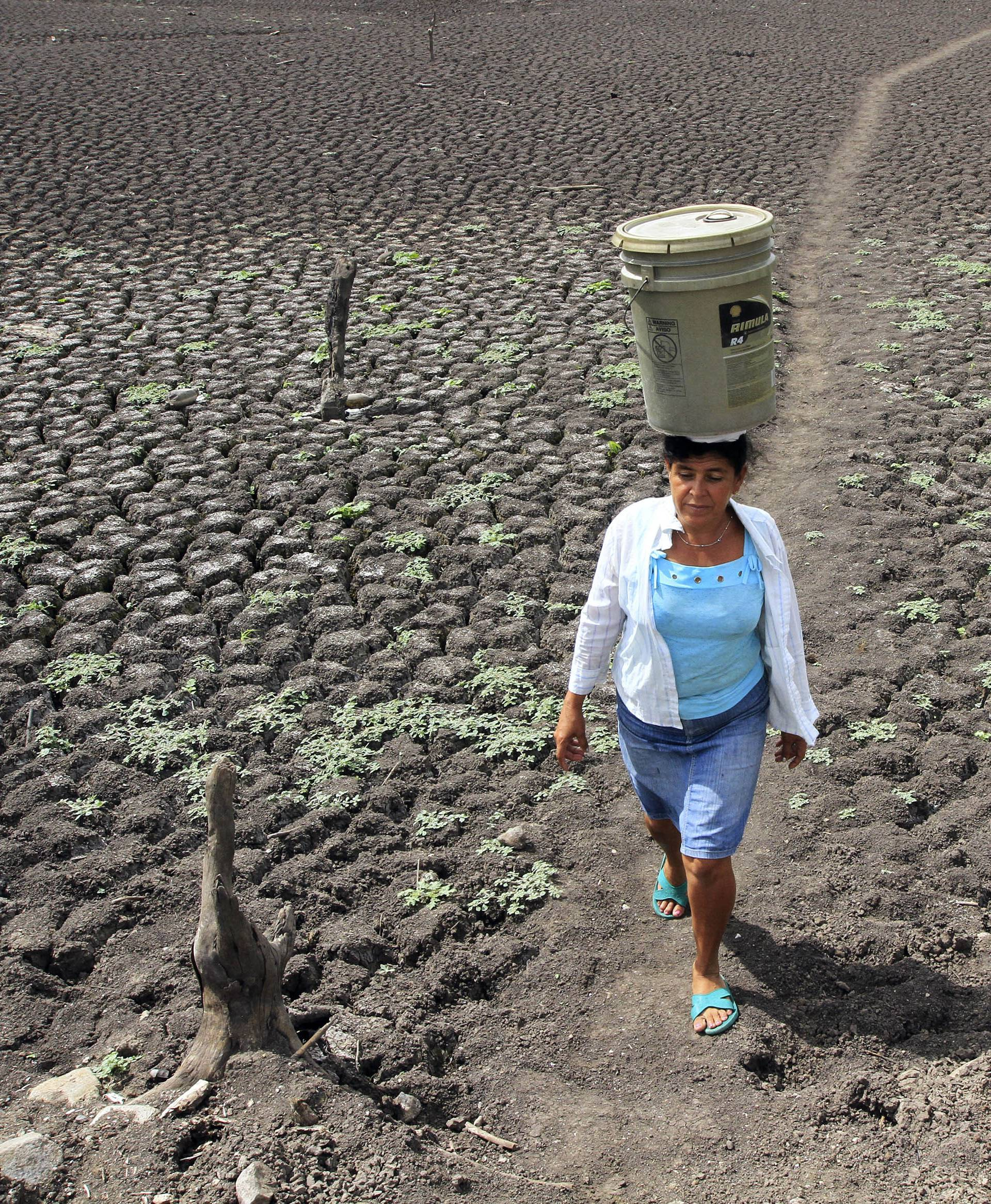 A woman carries a bucket of water on her head at Santa Isabel  town.