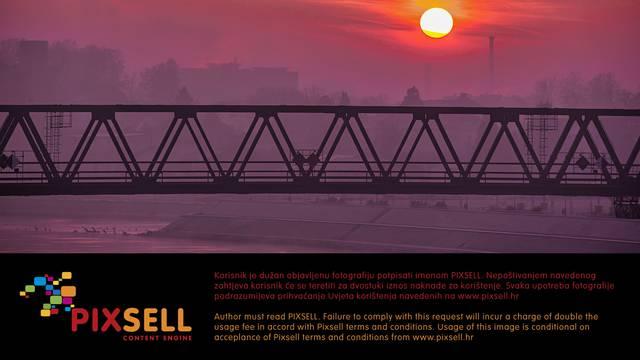 Izlazak sunca nad Dravom i željezničkim mostom u Osijeku