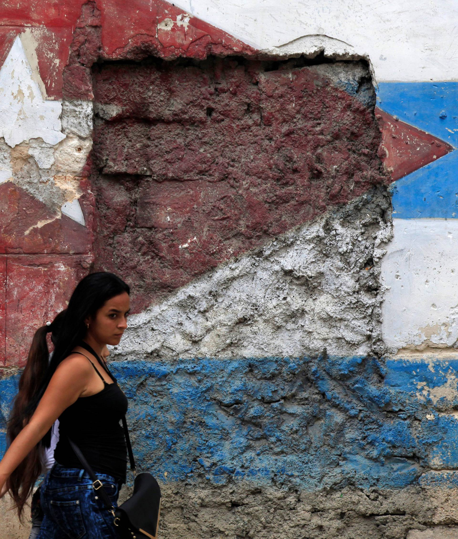 A woman walks in front of a mural of the Cuban flag in Havana, Cuba