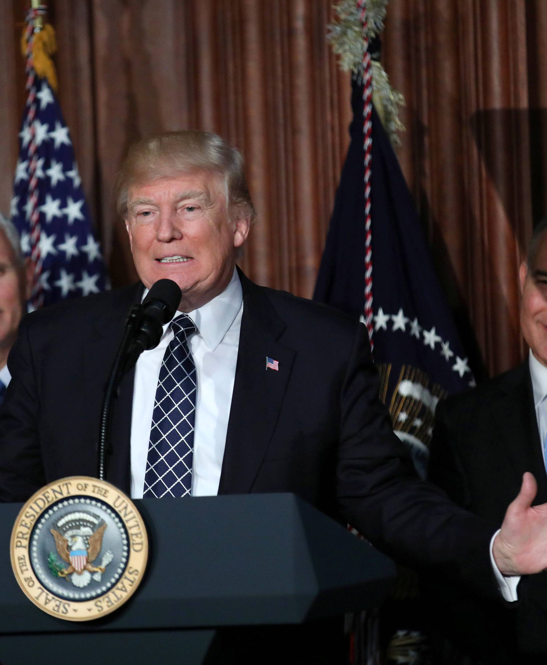 "U.S. President Donald Trump speaks between Vice President Mike Pence and EPA Administrator Scott Pruitt prior to signing an executive order on ""energy independence,"" eliminating Obama-era climate change regulations, during an event"