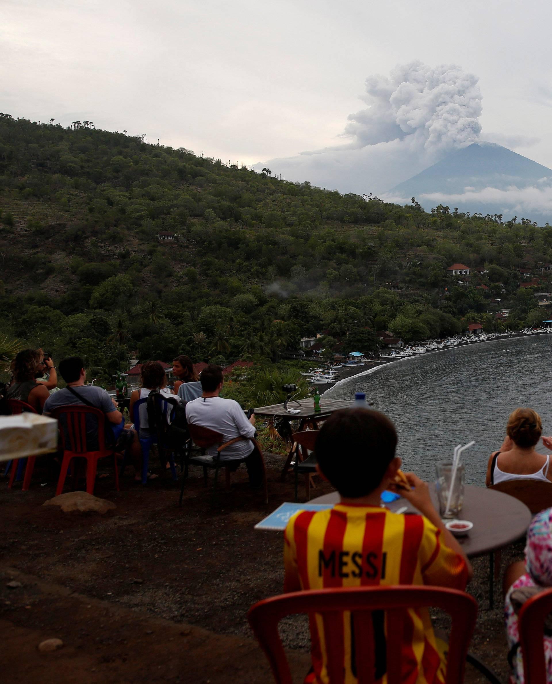 People watch Mount Agung volcano erupt from a cafe near Amed, Karangasem Regency, Bali