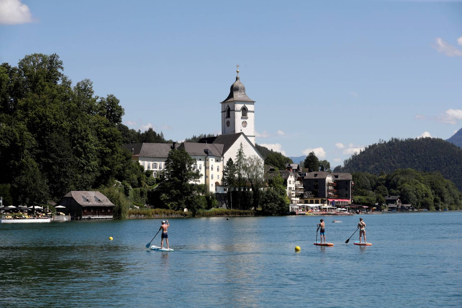 Stand-up paddlers are seen on Lake Wolfgangsee in front of St. Wolfgang