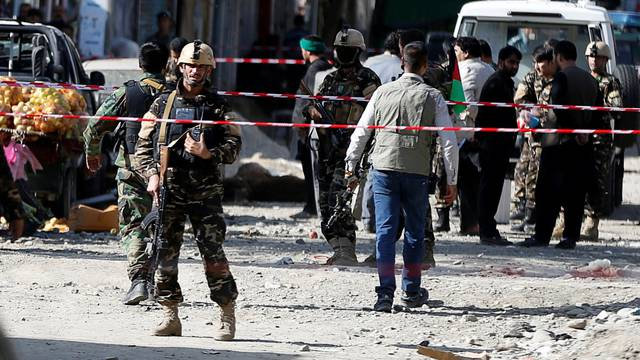 Afghan security forces inspect the site of a suicide attack near a large Shi'ite mosque, Kabul, Afghanistan