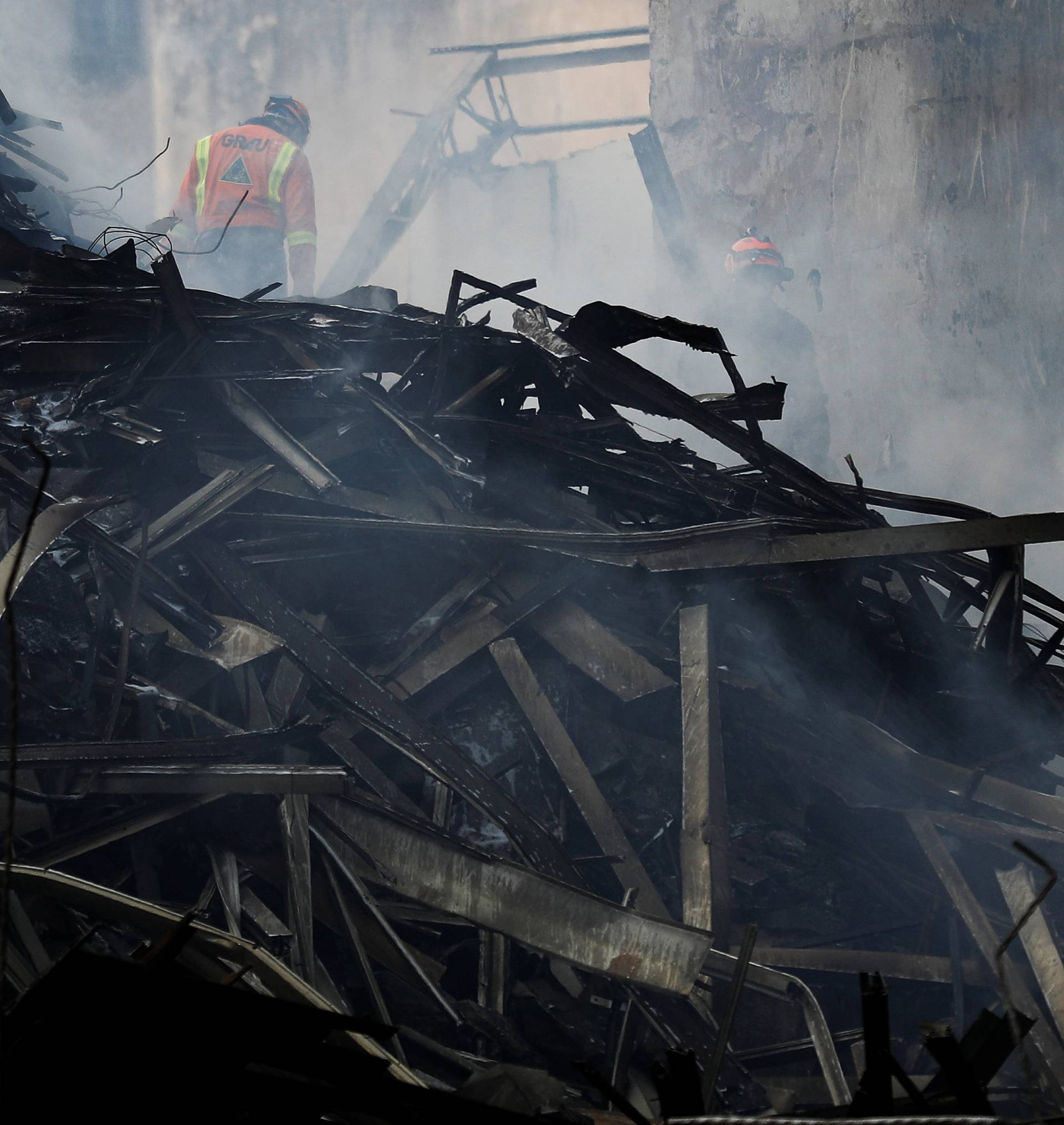 Firefighters try to extinguish a fire of a building that caught fire and collapsed in the center of Sao Paulo
