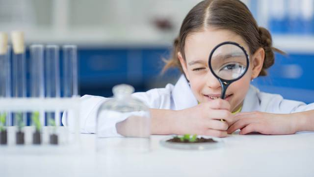 girl scientist holding magnifying glass and looking at camera