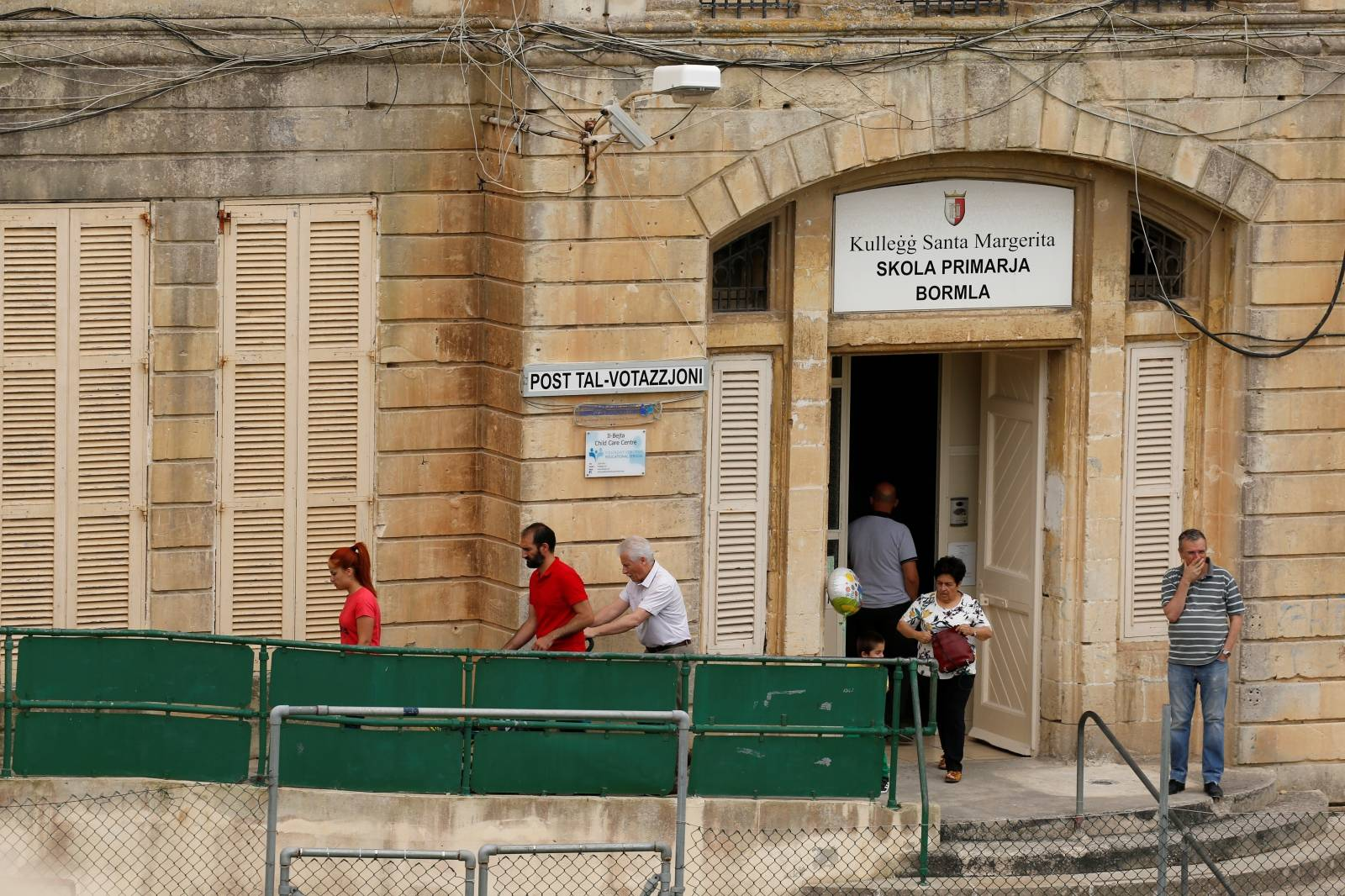 People leave a polling station after voting in European Parliament elections, in Cospicua