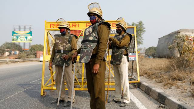 Police officers wait to check vehicles near New Delhi