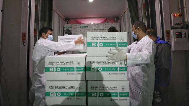 Workers transport boxes of COVID-19 vaccines from a truck to a cold storage facility in Guangzhou