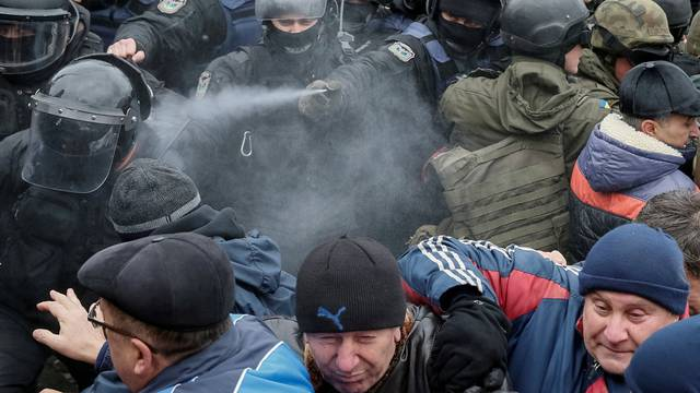 Police officers use tear gas against supporters of former Georgian President Saakashvili during clashes in Kiev