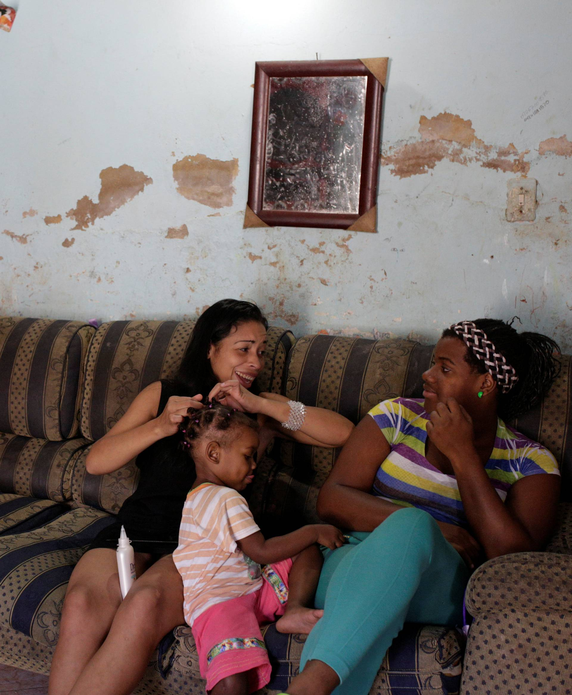 Women talk next to a Christmas tree in their home at the slum of Petare in Caracas