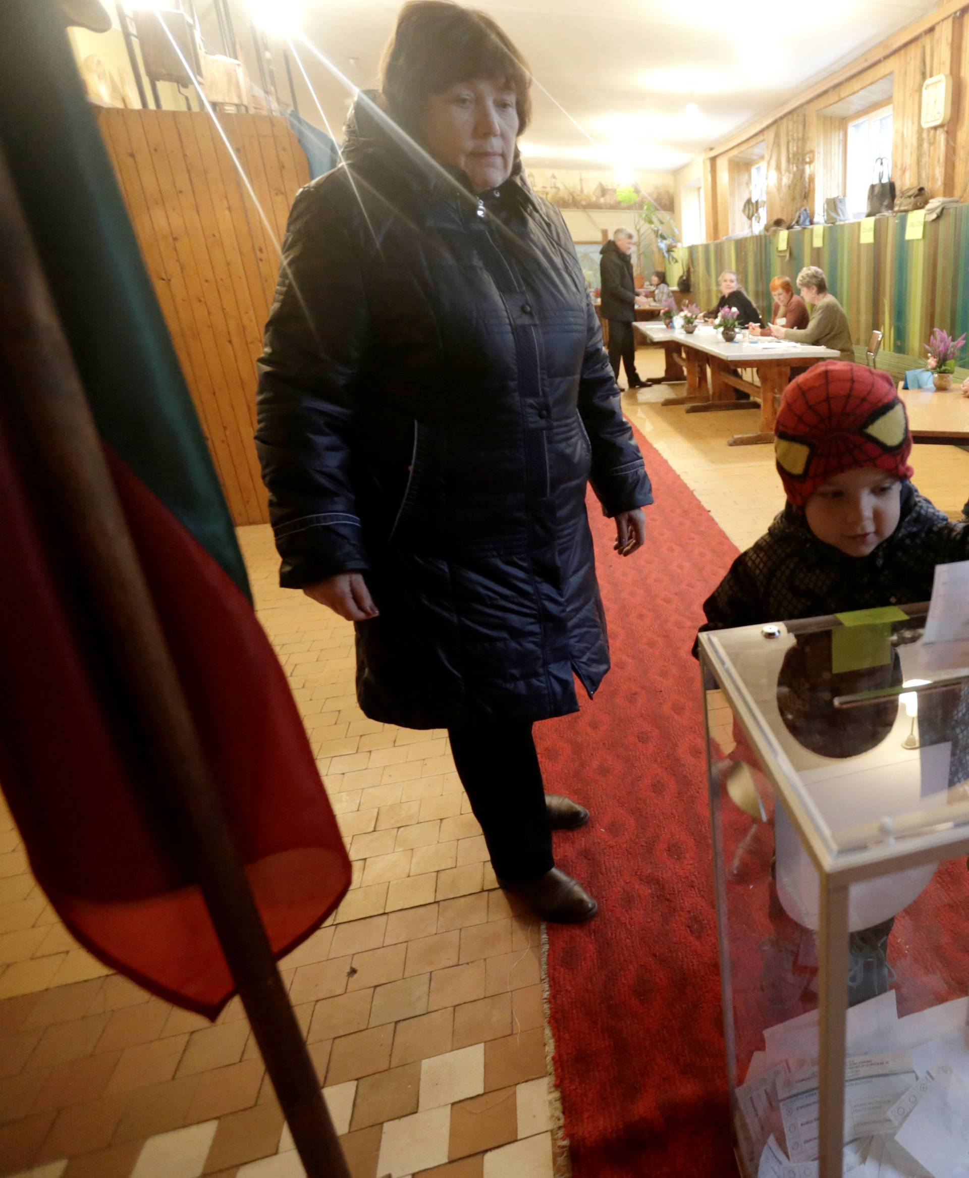 A woman looks on as a child casts her vote during a general election run-off in Birzai