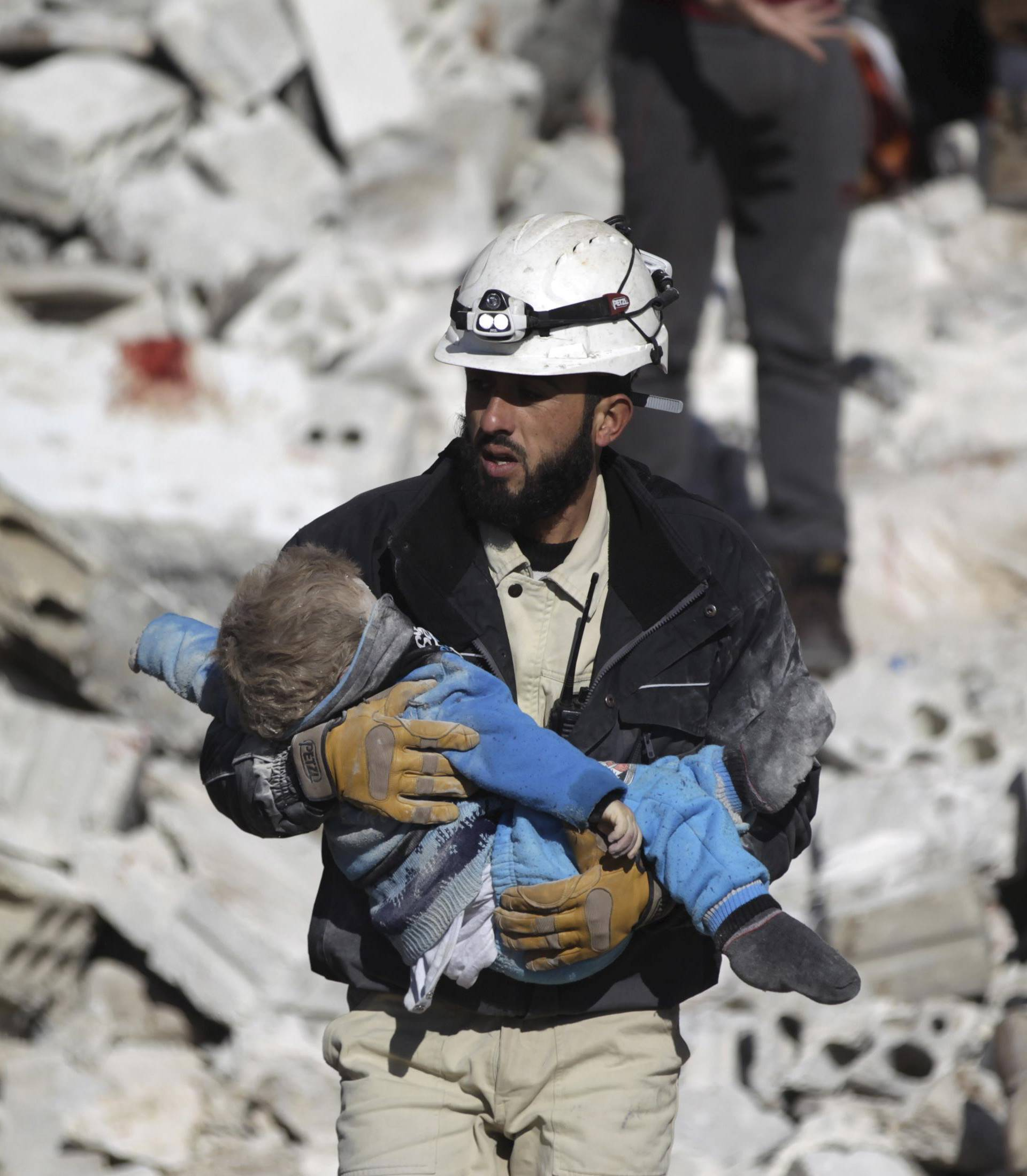 A civil defence member carries a dead child in a site hit by what activists said were airstrikes carried out by the Russian air force in the rebel-controlled area of Maaret al-Numan town in Idlib province, Syria