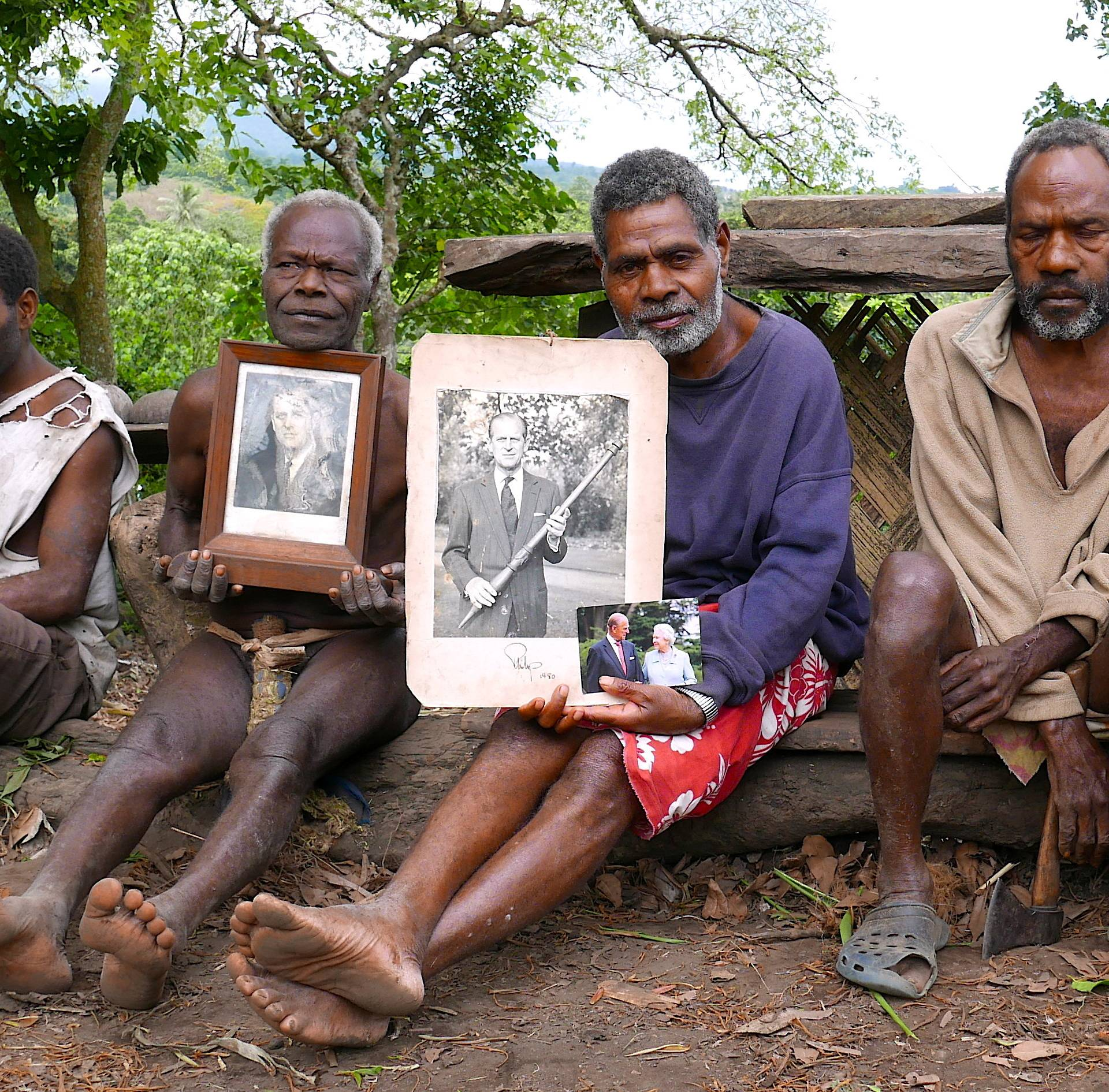 Chief Jack Malia from the Imanourane Tribe holds photographs of Britain's Prince Philip as he sits next to other villagers in the village of Younanen on Tanna Island in the Pacific island nation of Vanuatu