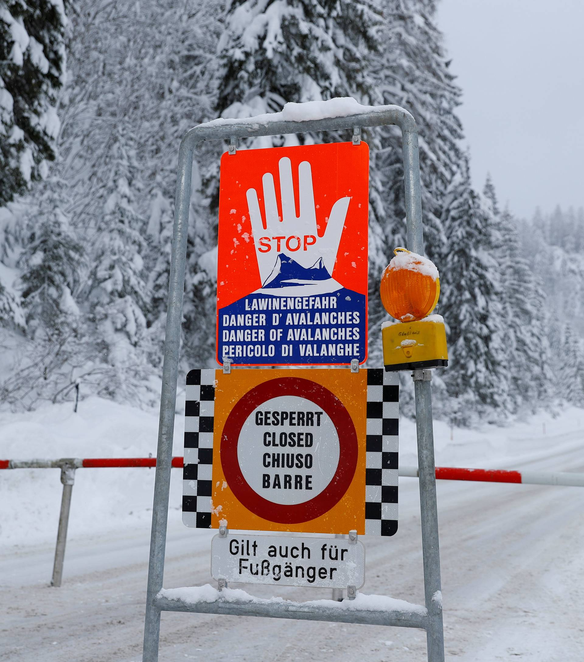 FILE PHOTO: A sign warning of avalanche danger is seen on a closed road after heavy snowfall near Obertauern, Austria