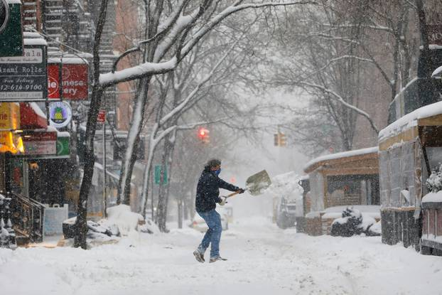 A person shovels snow in the Greenwich Village neighborhood in New York