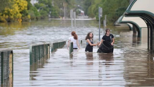 Locals walk through a flooded street in the northern New South Wales town of Lismore, Australia, after heavy rains associated with Cyclone Debbie swelled rivers to record heights across the region