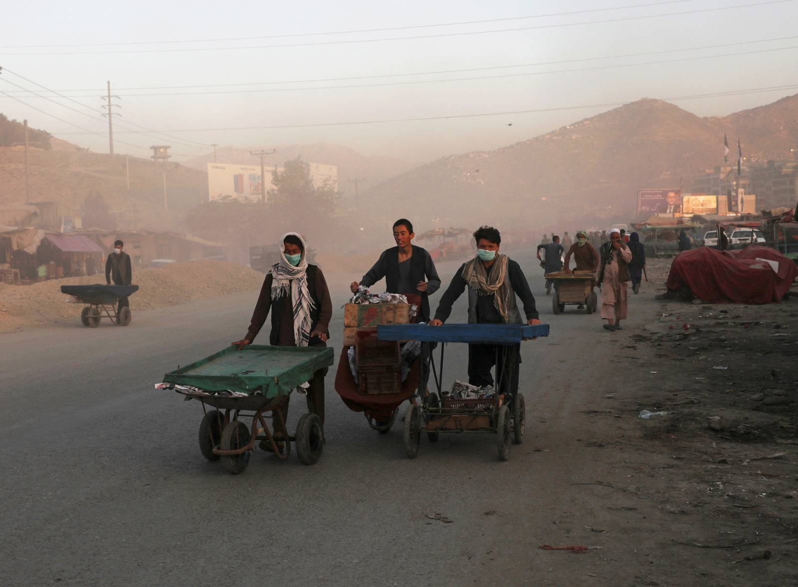 Afghan men push their hand carts in the early morning in Kabul