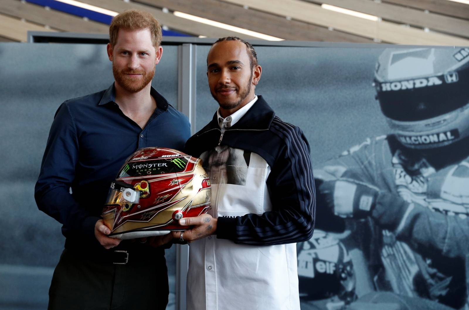 Britain's Prince Harry and Formula One World Champion Lewis Hamilton pose with one of Hamilton's helmet as they visit the Silverstone Experience at Silverstone circuit, in Towcester