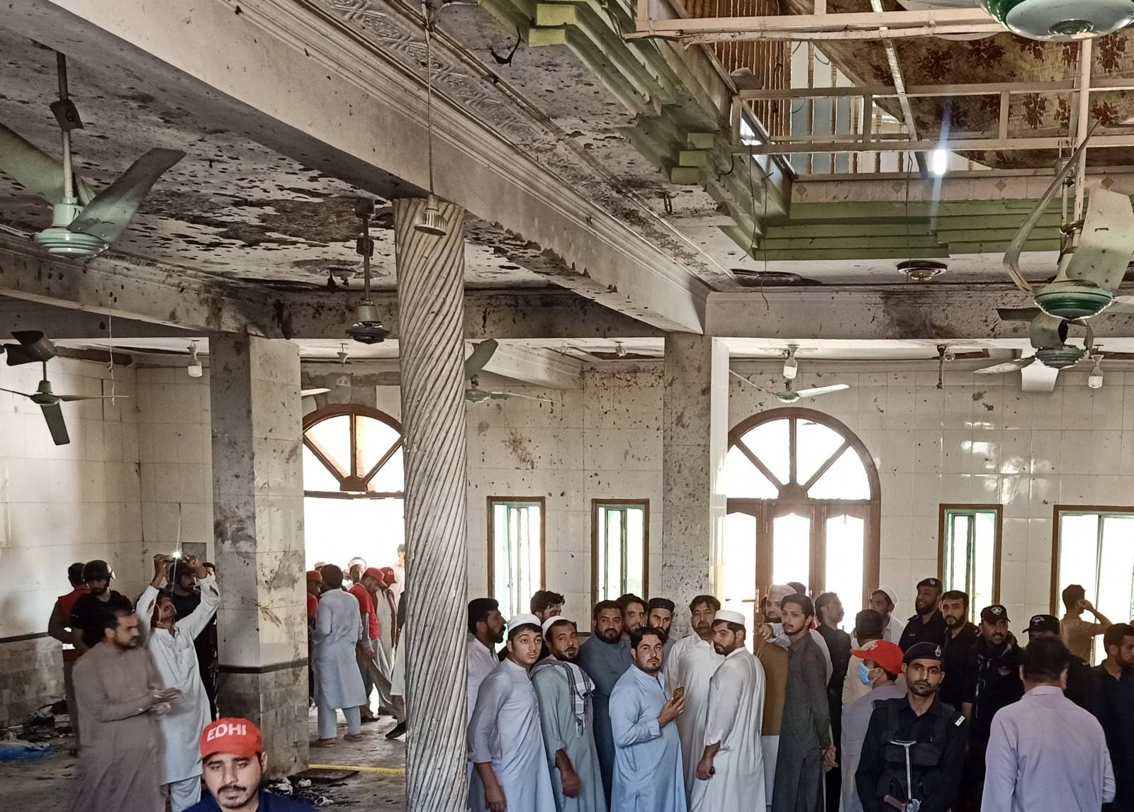 Residents and rescue workers gather at the site of a bomb blast at a religious seminary in Peshawar