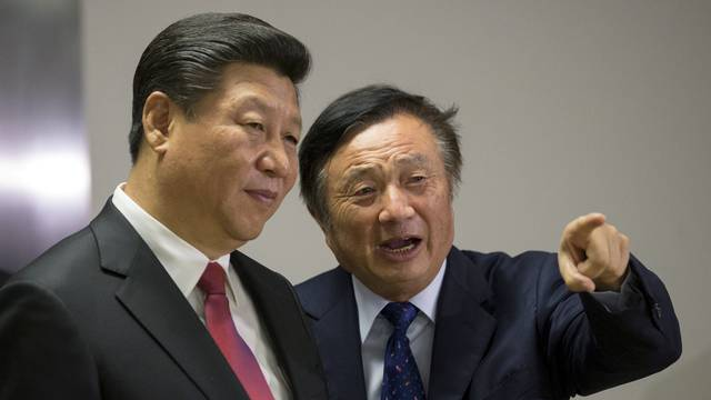 FILE PHOTO: Chinese President Xi Jinping pauses as he is shown around the offices of Huawei Technologies Co Ltd by Ren Zhengfei, president of Huawei, in London