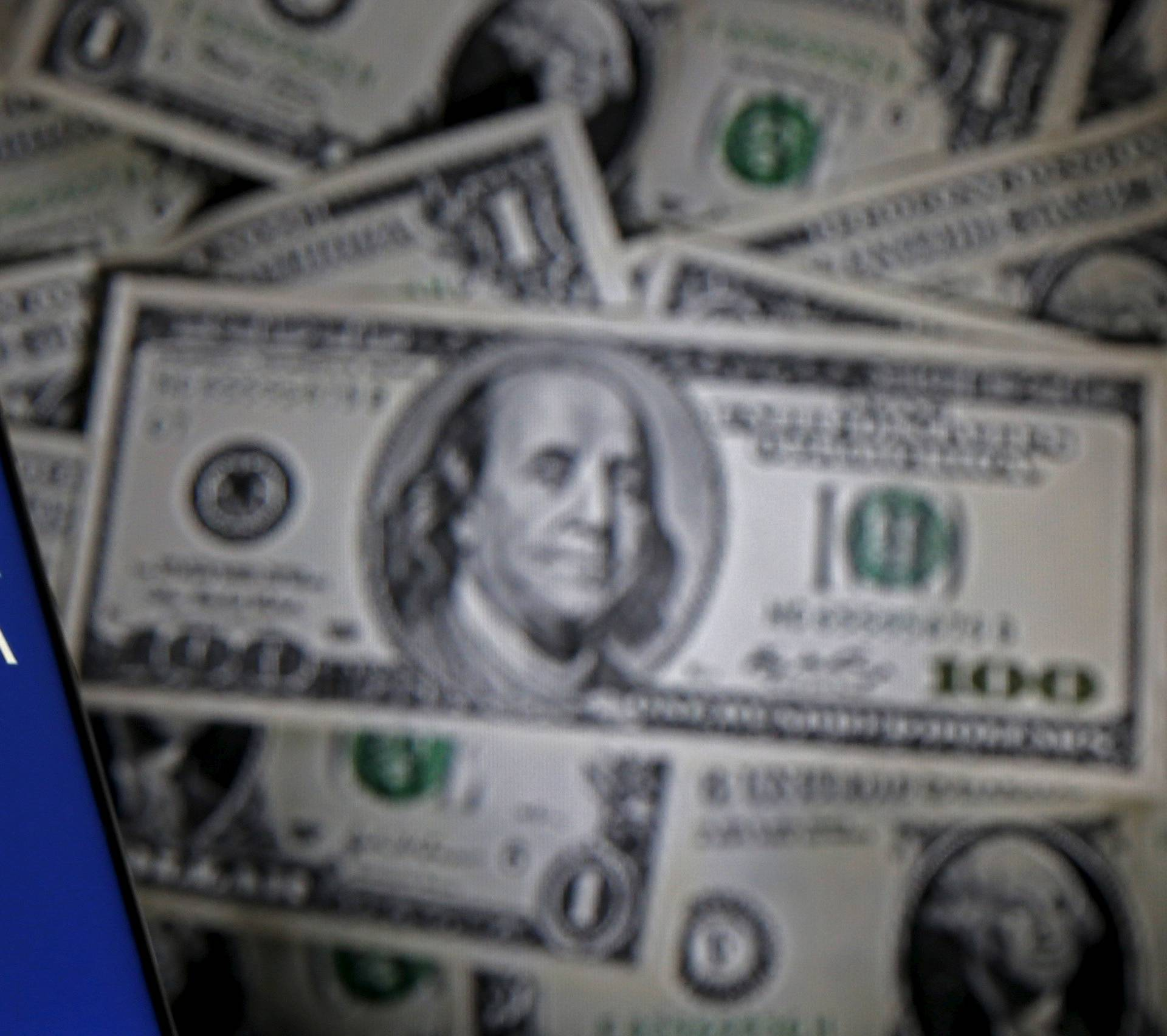 Picture illustration shows smartphone with Mossack Fonesca logo in front of a display of U.S. banknotes