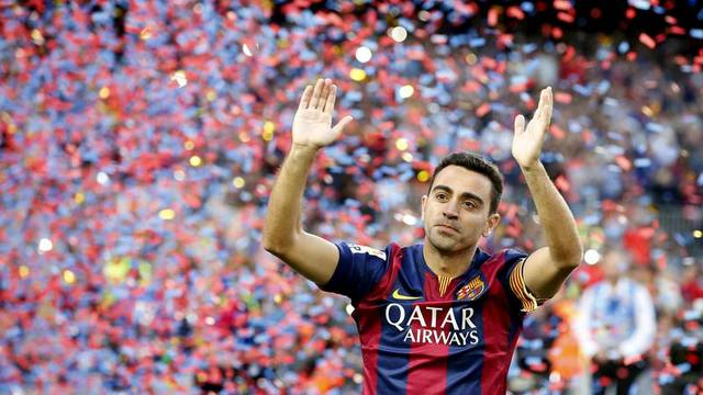 FILE PHOTO: Xavi Hernandez waves to Barcelona supporters after their Spanish first division soccer match against Deportivo de la Coruna at Camp Nou stadium in Barcelona
