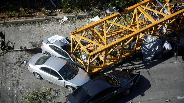 A member of the Seattle police department inspects one of the cars crushed by part of a construction crane on Mercer Street, which killed four people and injured several others in Seattle