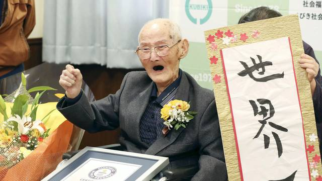 112-year-old Chitetsu Watanabe poses next to the calligraphy reading 'World Number One' after being awarded as the world's oldest living male by Guinness World Records, in Joetsu, Japan