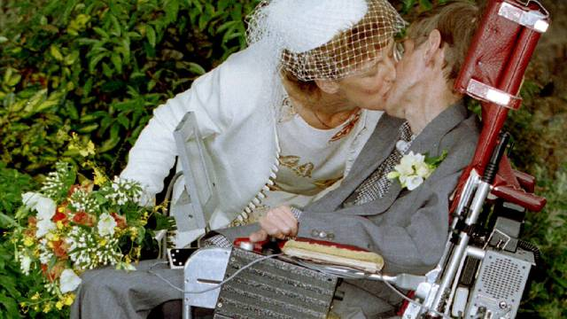A kiss for scientist and theorist Stephen Hawking from his new bride Elaine Mason after their civil ..