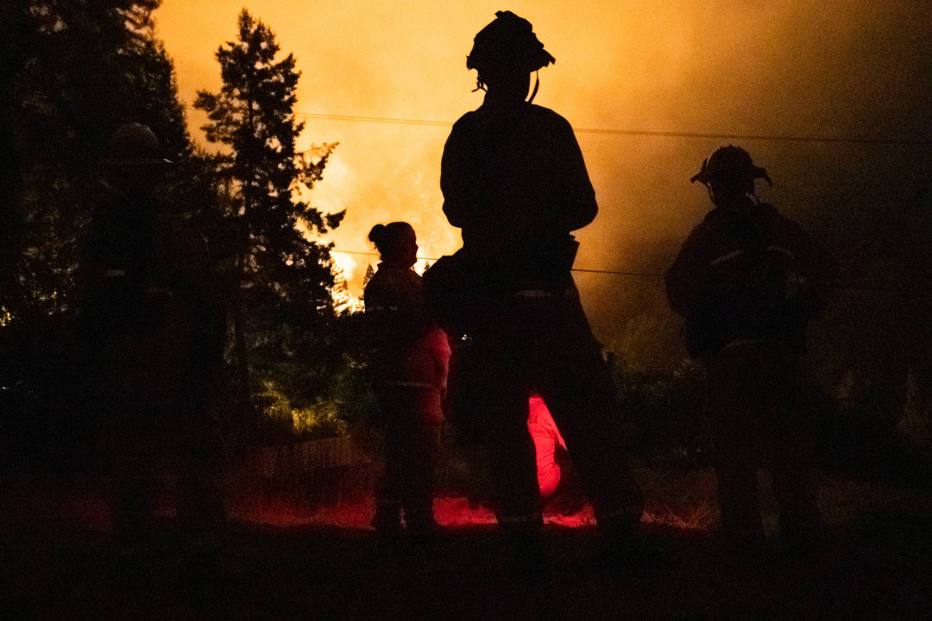 Santa Rosa firefighters monitor the LNU Lightning Complex Fire from a neighboring hilltop in Healdsburg, California
