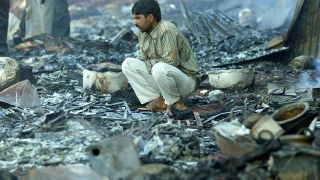 FILE PHOTO: A survivor sits among the debris of burnt shops near Mandherdevi temple in Wai village, southeast of Bombay, India