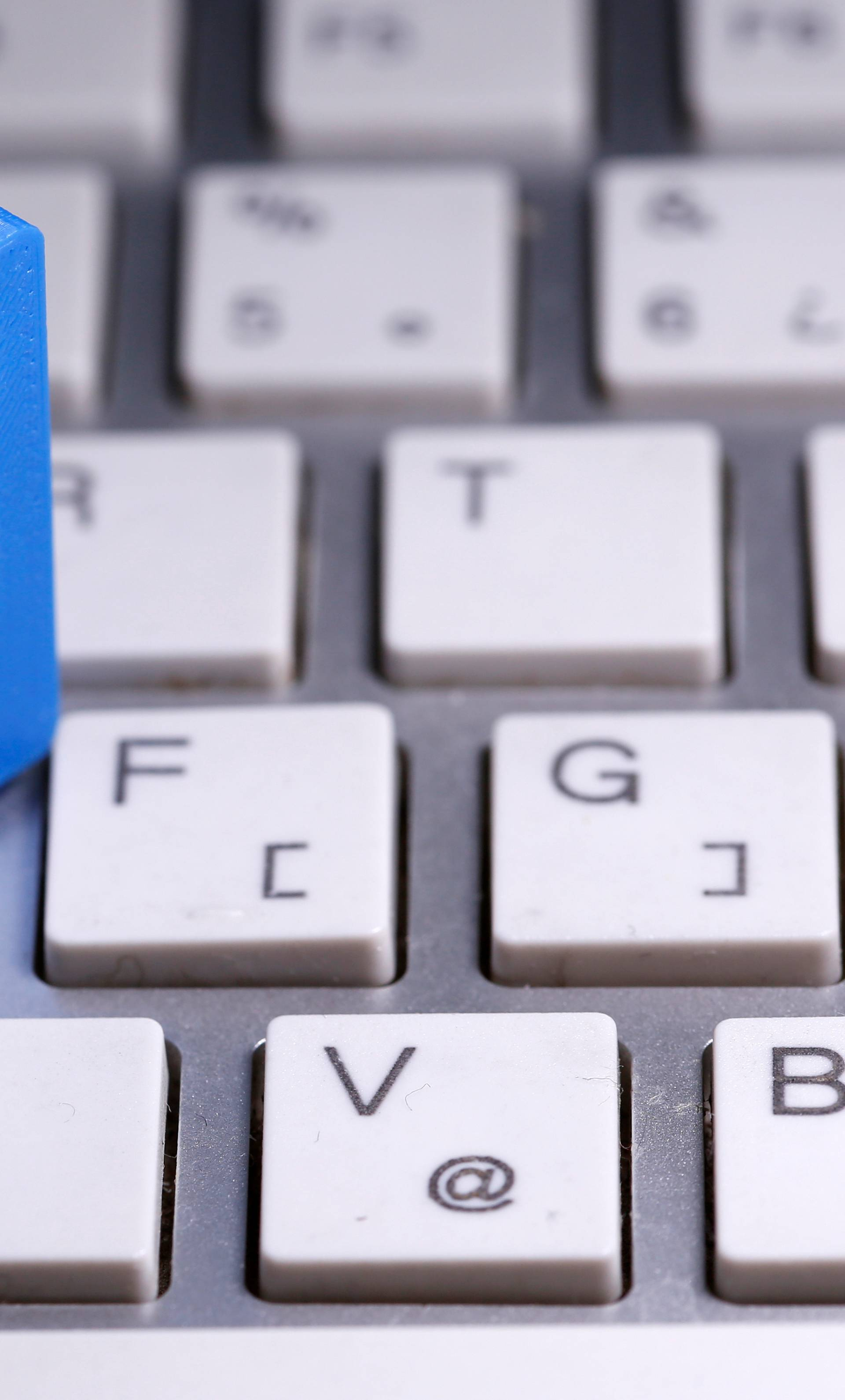 A 3D-printed Facebook logo is seen placed on a keyboard in this illustration