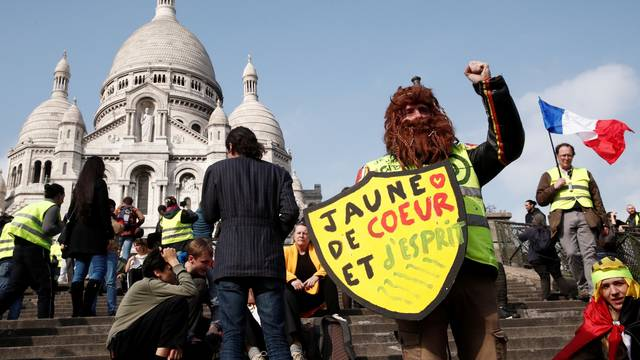 """Protesters wearing yellow vests attend a demonstration in front of the Sacre-Coeur Basilica of Montmartre during the Act XIX (the 19th consecutive national protest on Saturday) of the """"yellow vests"""" movement in Paris"""